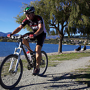 A biker cycles around a Lake Wanaka cycle track. Wanaka is  a year round destination set against the pristine alpine backdrop of Mount Aspiring National Park in Central Otago. South Island, New Zealand. 1st April 2011. Photo Tim Clayton.