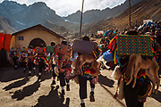Traditional dancers dance day and night in front of a small chapel during the celebration of the Lord of Qoyllur Rit'i (The Lord of the Shining Snow), in the background the Qullqipunku mountain in Cusco, Peru.