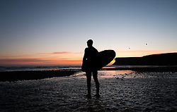 © Licensed to London News Pictures. 24/03/2014<br /> <br /> Saltburn, United Kingdom<br /> <br /> Surfer Martin Smith heads out at dawn for a surf at the beach in Saltburn by the Sea in Cleveland.<br /> <br /> Photo credit : Ian Forsyth/LNP
