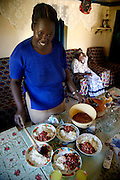Kibet Serem's sister-in-law Emily dishes up pinto beans and rice as Kibet Serem's mother, Nancy, watches a Kipsigis music video. (From the book What I Eat: Around the World in 80 Diets.)
