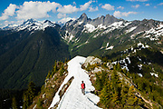 Ian Derrington hikes the summit ridge of Damnation Peak towards Mount Triumph, North Cascades National Park, Washington.