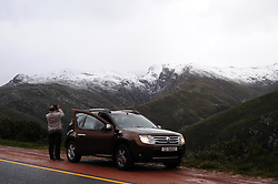 Cape Town - 180702 - A man is seen taking a picture of the snow on Franschoek Pass. Severe rainstorms lashed Cape Town and other parts of the drought-stricken Western Cape overnight, leading to severe flooding in places. Picture: Henk Kruger/ANA/African News Agency
