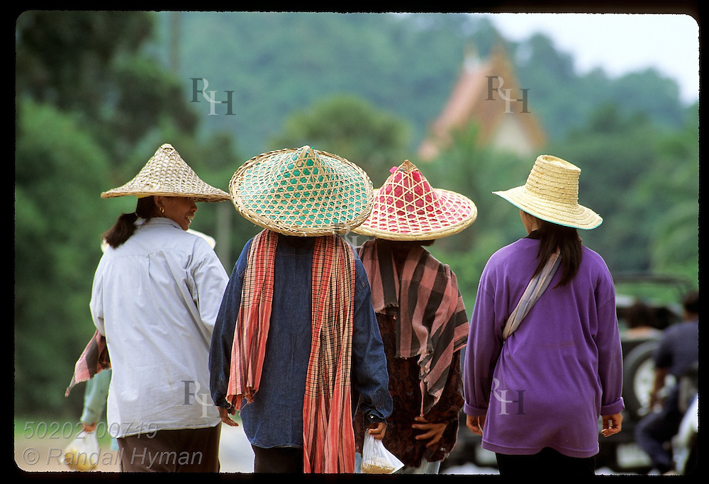 Women in colorful straw work hats walk home for lunch along highway on Phuket Island. (h) Thailand