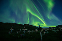 Northern Lights - Aurora Borealis shine in sky over wooden crosses of Tasiilaq cemetery, Greenland