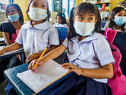"22 JANUARY 2018 - GUINOBATAN, ALBAY, PHILIPPINES: Students at Muladbucad Grande Elementary School in Guinobatan wear face masks in their 1st grade class. Several communities in Guinobatan were hit ash falls from the eruptions of the Mayon volcano and many people wore face masks to protect themselves from the ash. There were a series of eruptions on the Mayon volcano near Legazpi Monday. The eruptions started Sunday night and continued through the day. At about midday the volcano sent a plume of ash and smoke towering over Camalig, the largest municipality near the volcano. The Philippine Institute of Volcanology and Seismology (PHIVOLCS) extended the six kilometer danger zone to eight kilometers and raised the alert level from three to four. This is the first time the alert level has been at four since 2009. A level four alert means a ""Hazardous Eruption is Imminent"" and there is ""intense unrest"" in the volcano. The Mayon volcano is the most active volcano in the Philippines. Sunday and Monday's eruptions caused ash falls in several communities but there were no known injuries.    PHOTO BY JACK KURTZ"