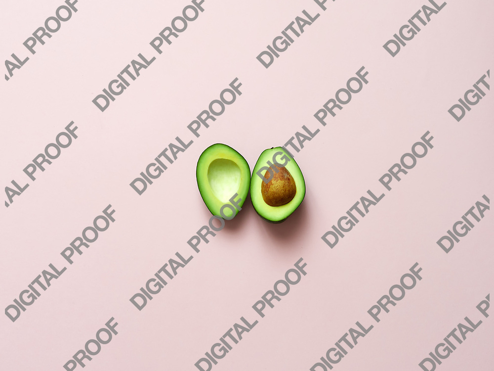 Avocado sliced with seed isolated in pink background viewed from above - flatlay look