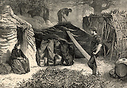 Charcoal burners in Epping Forest, Essex, near London, England.  The men and their families lived in the forest for the summer so that they could be on hand to attend the burning clamps whenever necessary. On the left a woman sits on a log outside the rough hut which would be her summer home.  On the right is a screen to regulate the draught.  Engraving from 'The Illustrated London News' (London, 8 November 1879).