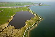 Nederland, Noord-Holland, Gemeente Amsterdam, 28-04-2010; IJsselmeerdijk of Uitdammerdijk met Het Barnegat. De zogenaamde open braak is het restant van een eerdere dijkdoorbraak en vermoedelijk ontstaan bij de dijkdoorbraak van de Waterlandse zeedijk in 1570 (Allerheiligenvloed). Het meertje is nu beschermd natuurgebied..IJsselmeerdijk or Uitdammerdijk with the Barnegat. The open 'breach' is a remnant of an earlier levee failure and probably results from the Saints Flood in 1570..luchtfoto (toeslag), aerial photo (additional fee required).foto/photo Siebe Swart