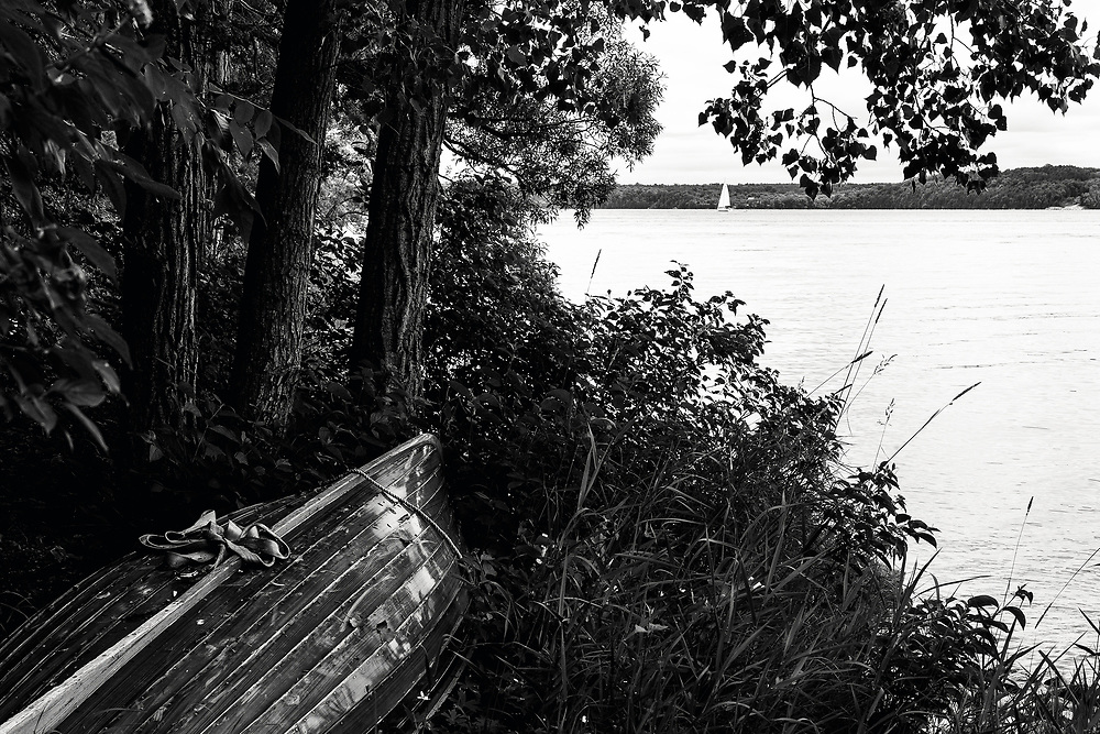 A wooden canoe on the shoreline of Lake Ontario. The Loyalist Parkway between Picton and Kingston, Ontario
