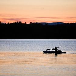 A kayaker at sunset at Umbagog Lake State Park, Cambridge, New Hampshire.