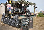 Blackboard offers for fresh fish on sale outside beach shed, Aldeburgh, Suffolk, England