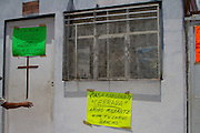 """Migrants shelter  """"San Juan Diego Cuauhtlatoatzin"""" is closed in Lecheria, Estado de México on July 9th, 2012. In its walls, painted white by neighboors, it can be read in placards: """"House of migrant 'Closed'. Friend migrant, continue your way"""". (Photo: Prometeo Lucero)"""