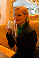 Young German woman drinking coffee at Cafe Gloria, Leipzig, Saxony, Germany