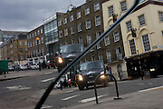 Double image of a van turning a street corner caused by the split, broken mirror lying on the ground with its diagonal crack