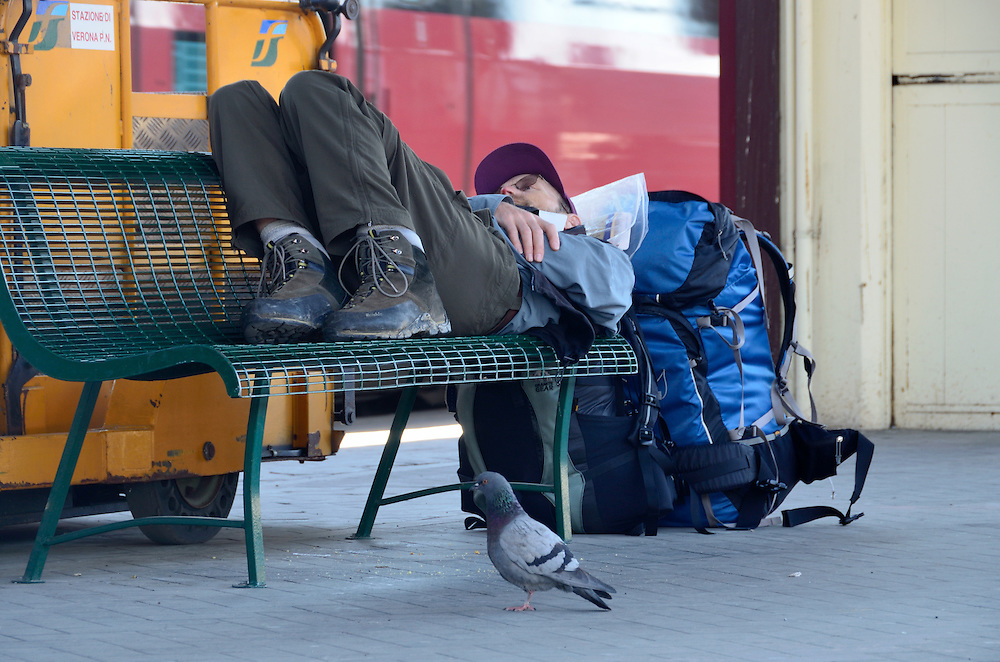 Traveler laying on a bench on the platform of a train station in Italy.