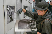 """Portland, Oregon, USA. 26 FEB, 2018. A performance artist cuts the work of the photographer Robert Frank from the wall at Blue Sky Gallery in Portland, Oregon, USA. The work was destroyed in a """"Destruction Dance"""" performance defacing the photographs with ink and mutilation with scissors, knives and even ice skates  at the end of it's run. The destruction was Frank's protest regarding today's greed in the global art market."""
