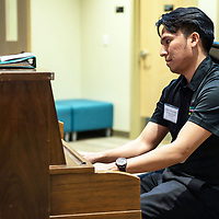 Rehoboth Christian School alumni Jordan Yazzie, 25, plays the piano for guests as they enter the school for the evenings festivities on Friday in Rehoboth.