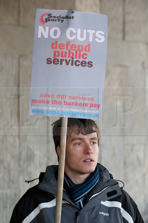© under license to London News Pictures.  06/12/2010. A man holds a sign outside the Civic Centre today (Monday). People gather outside the Civic Centre in Plymouth to protest against public service cuts.