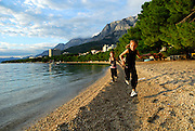Two children (9 years old and 5 years old) running along beach in late afternoon sun, with the Biokovo National Park, part of the Dinaric Alps, in the background. Makarska, Croatia