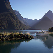 The Milford Adventurer returns to harbour after a tourist cruise on Milford Sound with Mitre Peak in the background.  Mitre Peak is an iconic mountain in the South Island of New Zealand. It is one of the most photographed peaks in the country. Part of the reason for its iconic status is its location. Close to the shore of Milford Sound, in the Fiordland National Park in the southwestern South Island, it is a stunning sight. Rising to 1,692 metres from the water of the sound. it is actually a closely grouped set of five peaks, although from most easily accessible viewpoints it appears as a single point. Milford Sound,  Milford Sound, New Zealand. 29th April 2011. Photo Tim Clayton