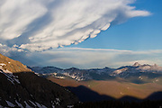 "Lumpy mammatus (""mammary"") clouds build on the underside of a storm cloud reaching over distant Longs Peak and Rocky Mountain National Park, as seen from Baker Gulch, Never Summer Wilderness, Colorado."