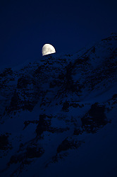 """© Licensed to London News Pictures. 11/04/2014. The Moon drops behind """"Flat Mountain"""" at 1.50 am in Longyearbyen, Svalbard. Photo credit : Mike King/LNP"""