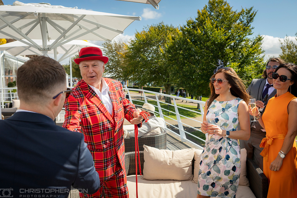 Magician Adrian Wright performing for guests at Goodwood Racecourse.<br /> Picture date: Saturday August 28, 2021.<br /> Photograph by Christopher Ison ©<br /> 07544044177<br /> chris@christopherison.com<br /> www.christopherison.com<br /> <br /> IMPORTANT NOTE REGARDING IMAGE LICENCING FOR THIS PHOTOGRAPH: This image is supplied to the client under the terms previously agree. No sales are permitted unless expressly agreed in writing by the photographer.