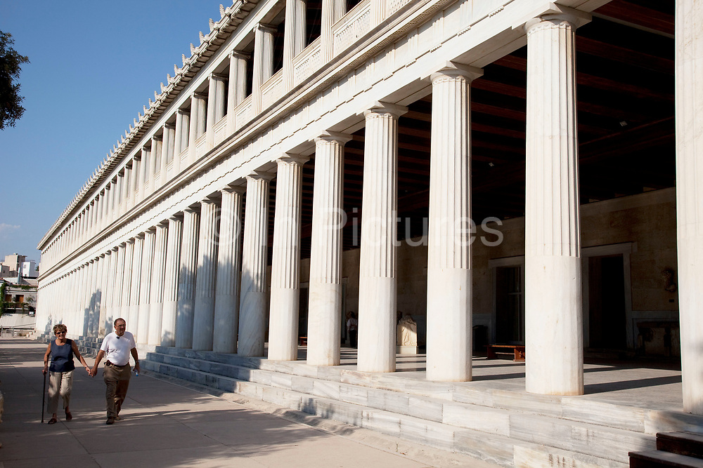 Elderly couple at The Stoa of Attalos or Attalus located in the east side of archaeological site of the Ancient Agora in Athens just oposite the Adrianou street in Monastiraki. The Stoa of Attalos was built around 150 BC, by Attalos II, King of Pergamos as a donation to Athens. The construction of the building began in 159 BC and ended in 138 BC. The building was the largest in length in Greece during the antiquity. It was rebuilt in the same style and shape from 1953 to 1956 with beautifully crafted marble columns. It is recognised as one of the most impressive stoa in the Athenian Agora. Typical of the Hellenistic age, the stoa was more elaborate and larger than the earlier buildings of ancient Athens. The stoa's dimensions are 115 by 20 metres wide (377 by 65 feet wide) and it is made of Pentelic marble and limestone. The building skillfully makes use of different architectural orders. The Doric order was used for the exterior colonnade on the ground floor with Ionic for the interior colonnade. Athens is the capital and largest city of Greece. It dominates the Attica periphery and is one of the world's oldest cities, as its recorded history spans around 3,400 years. Classical Athens was a powerful city-state. A centre for the arts, learning and philosophy.