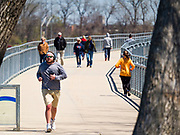 19 APRIL 2020 - DES MOINES, IOWA: People walk around Gray's Lake, a popular public park and lake south of downtown Des Moines. After a week of colder than normal weather, including three inches of snow, the weekend was spring like and people went to public parks to enjoy the pleasant weather.        PHOTO BY JACK KURTZ