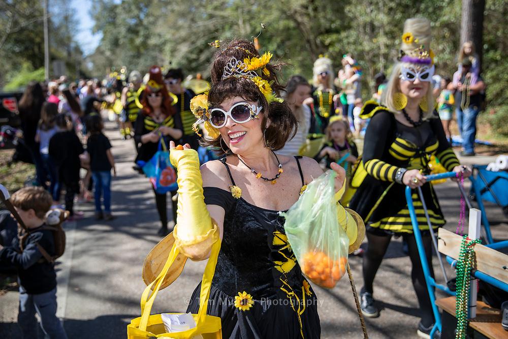 Abita Queen Bee Rachel Lambert marches along Main Street during the Krewe of Push Mow parade in Abita Springs, La.