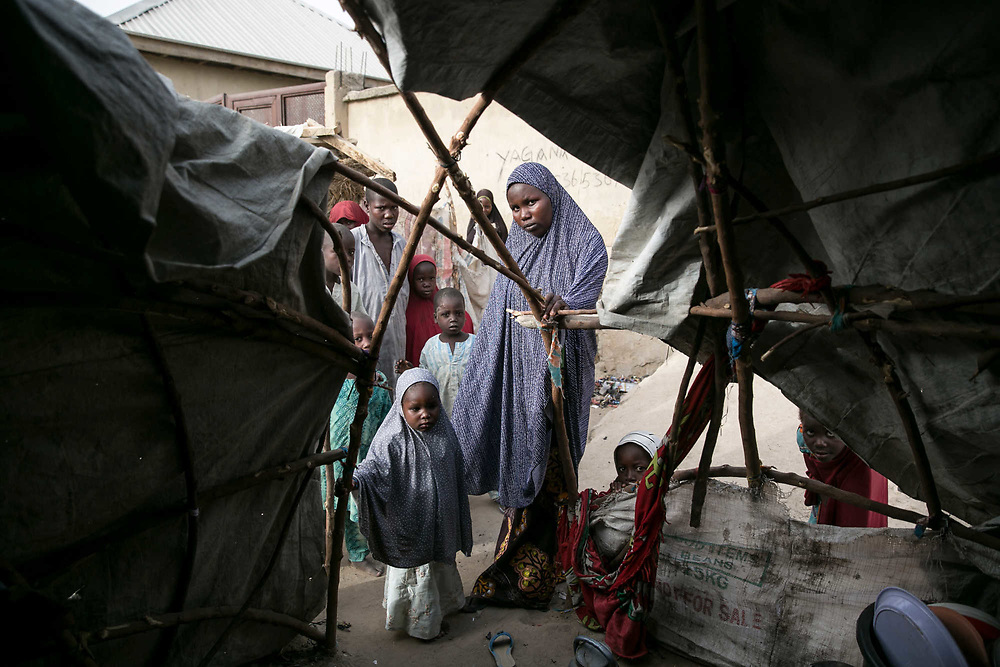 Yagana, 23, holds one of the wooden frames of her makeshift tent with her daughter whom she was conceived by a Book Haram fighter, in an IDP camp in Maiduguri, Nigeria, April 20, 2019. Yagana was abducted by four Boko Haram fighters in Mafa Local Government in 2014 and taken to the Sambisa Forest. When the Nigerian Military attacked their hideout in 2015, she was rescued by the army and gave birth to a baby in the military detention center in Giwa. As she was forced to leave the secondary school by BH, she wanted to continue her education and took a graduation exam on April 26, 2019.