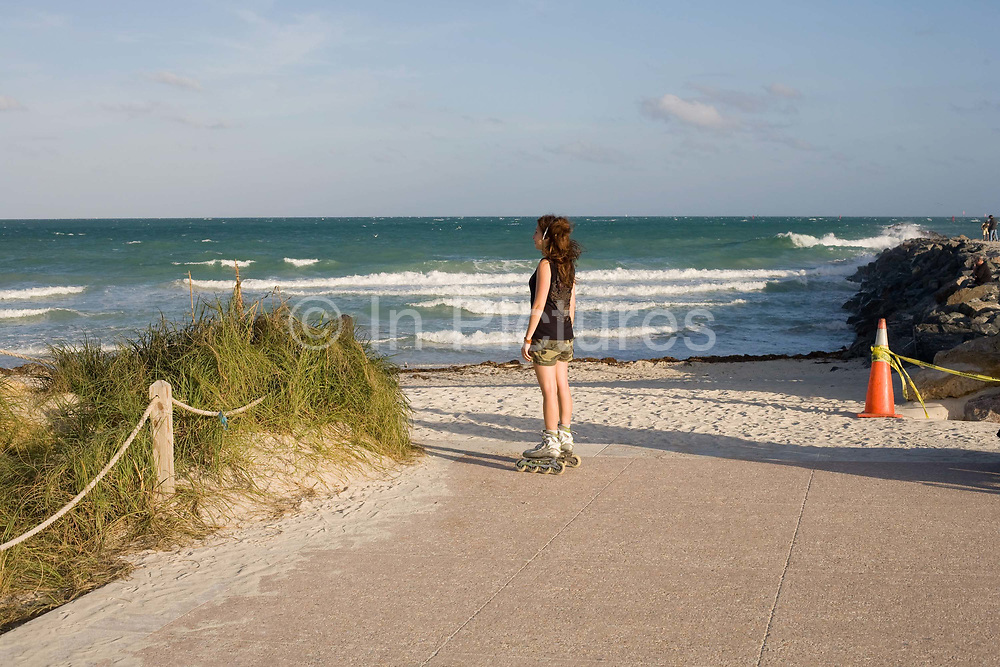 A young woman on rollerblades stands taking in the sea air and looking out across the Atlantic Ocean from South Pointe South Beach Miami