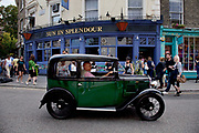 An old vintage Austin car on Portobello Road, Notting Hill, West London. This famous Sunday market is when the antique stalls come out as well as the food stalls.