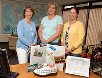 """Anne Cote, Marie Caprario and Kim Terrio of Penny Pitou Travel display their """"cruise shoe"""" creation made by Sandy Percy during the Downtown Still Has Sole event which will be ongoing through Thursday.  (Karen Bobotas/for the Laconia Daily Sun)"""