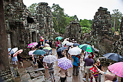 Tourists with umbrellas visit Angkor Thom, ancient Hindu temples, in the monsoon season at Siem Reap, Cambodia.
