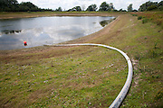 Irrigation pipe water reservoir lake at low level in summer Sutton, Suffolk, England, UK
