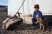 Kazakhs with wolf cub pet<br /> Largest ethnic minority and eagle hunters<br /> near Tsengel Khairhkhan Mountains<br /> Western Mongolia