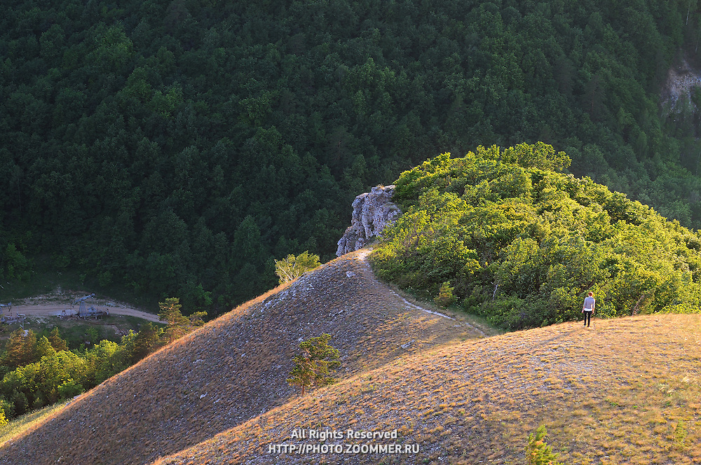 """View down to steep hills of Zhiguli mountains with girl on a track. Russian National Park """"Samara Luka""""."""