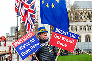 """January 30, 2020, London, England, United Kingdom: Anti-Brexit campaigner holds placards outside Parliament in London, Thursday, Jan. 30, 2020. Although Britain formally leaves the European Union on Jan. 31, little will change until the end of the year. Britain will still adhere to the four freedoms of the tariff-free single market """" free movement of goods, services, capital and people. (Credit Image: © Vedat Xhymshiti/ZUMA Wire)"""