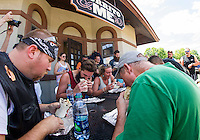 """Alex Cancel and Jenna Russell have a quick bite at Burrito Me in Veteran's Square during their annual """"burrito eating"""" contest on Thursday afternoon.  (Karen Bobotas/for the Laconia Daily Sun)"""