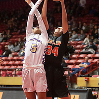 Kirtland Central Bronco Aisha Ramone (5) and Gallup Bengal Jordan Joe (34) reach for a rebound during their 4A girls NMAA State Basketball quarterfinal playoff game at Dreamstyle Arena (The Pit) Tuesday night in Albuquerque. The Broncos beat the Bengals 61-54 to advance to the semifinal round.
