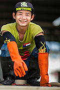 20 JUNE 2014 - SAMUT SAKHON, SAMUT SAKHON, THAILAND: A Burmese migrant worker in a shrimp processing center in Samut Sakhon. Hundreds of thousands of migrant workers from Myanmar work in the Thai fishing industry. Samut Sakhon, (sometimes still called Mahachai, its historical name) is a large fishing port. Many Burmese live in the town and work in the fish process plants. Although hundreds of thousands of Cambodians fled Thailand last week after the military coup, the Burmese workers have stayed and are still working in many Thai towns.    PHOTO BY JACK KURTZ