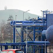 Nederland Barendrecht 29 november 2008 20081129 Foto: David Rozing ..TOT 6 DECEMBER GEEN PUBLICATIE VAN DEZE BEELDEN ..Serie demonstratie project ondergrondse Co2 opslag Shell Barendrecht ..NAM in Barendrecht. Op het terrein staat een gaswinninginstallatie, hiermee wordt het gas dat zich onder Barendrecht bevindt naar boven gehaald. Zodra de 2 gasvelden leeg zijn zullen deze gebruikt gaan worden voor de ondergrondse opslag van CO2. Dit gebeurt met dezelfde installatie. .Shell Nederland Raffinaderij B.V. (SNR) heeft het initiatief genomen voor een demonstratieproject in samenwerking met Nederlandse Aardolie Maatschappij ( NAM ). Daarbij is het de bedoeling dat pure CO2 die bij de raffinaderij in Pernis bij de productie van waterstof vrijkomt, per pijpleiding naar Barendrecht wordt getransporteerd. Vervolgens wordt de CO2 in lege aardgasvelden geïnjecteerd voor permanente opslag..OCAP?De Shell exploiteert momenteel de nu nog deels gevulde aardgasvelden Barendrecht en Ziedewij en heeft een grote kennis van de ondergrond en injectie van aardgas in bestaande velden.Het is de bedoeling dat OCAP ook het transport van CO2 naar Barendrecht gaat verzorgen..Shell CO2 Storage B.V.?Voor het project is een nieuw bedrijf opgericht, Shell CO2 Storage B.V. (SCS). SCS zal verder ook zekerstellen dat alle aanwezige kennis over de Barendrechtse velden ten volle kan worden benut bij de opslag van CO2 en de daaraan gekoppelde monitoring.Het Barendrecht-veld?Shell en OCAP hebben net zoals andere organisaties veel onderzoek gedaan naar het transport naar en de mogelijke CO2-opslag in lege aardgasvelden. Vanwege de ligging, dichtbij de CO2-bron van Pernis, hebben de partijen uiteindelijk gekozen voor het aardgasveld Barendrecht (ten zuidwesten van Rotterdam). Als de ervaringen met het Barendrecht-veld goed zijn, zal in een later stadium Barendrecht Ziedewij het tweede veld zijn dat in aanmerking komt voor CO2-opslag. Uit deze aardgasvelden wordt nu nog gas gewonnen. Zodra de productie stopt