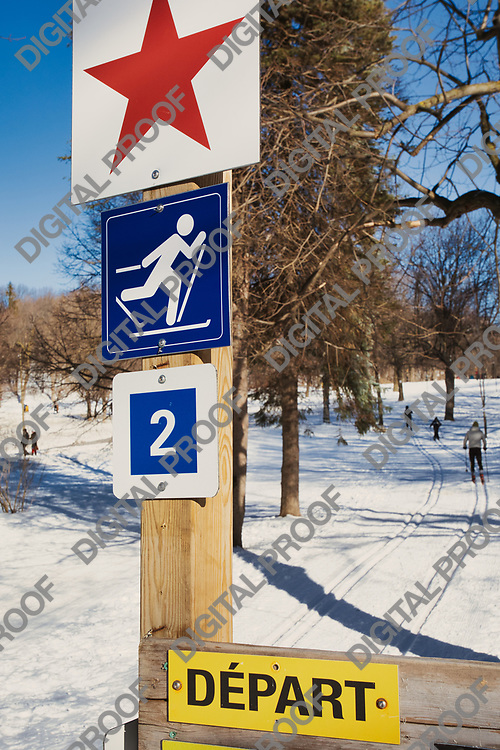 January 09, 2021 - Montreal, Canada Signs of Cross Country Ski tracks with skiers in the background at Mont-Royal Montreal in winter
