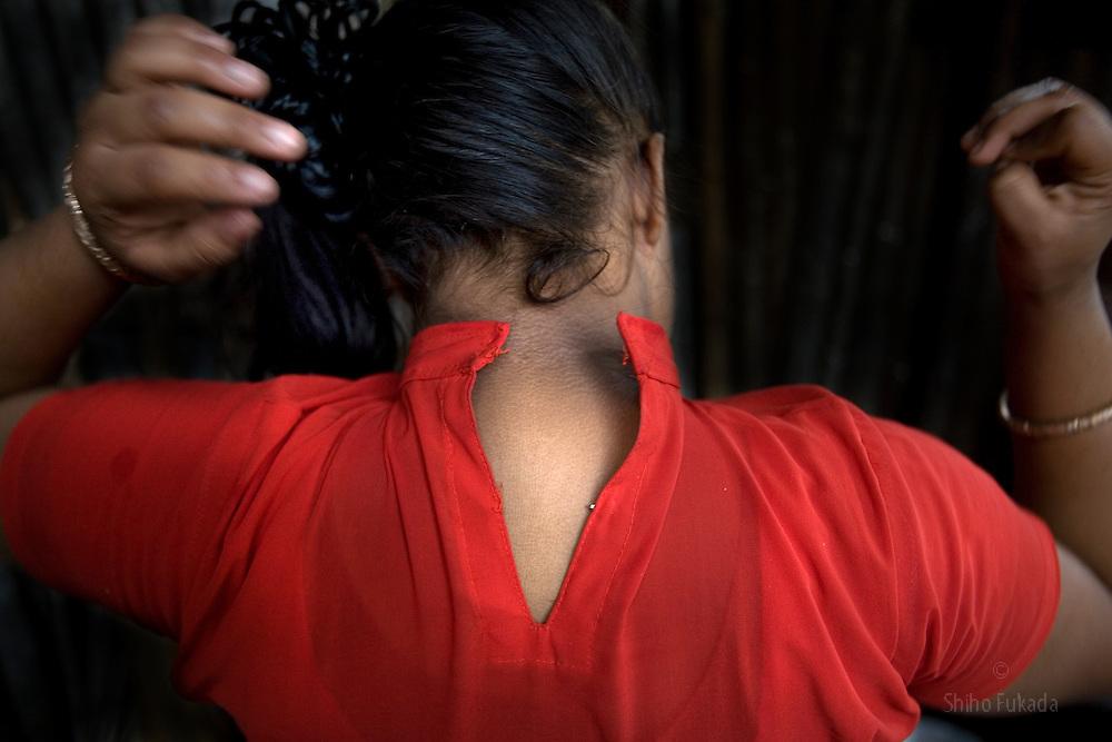 Sex worker Munnie, 15, unbuttons her shirt at brothel in Tangail, Bangladesh.