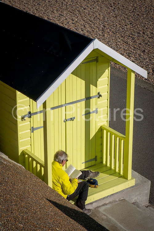 A man in a yellow jacket sits in the doorway of a yellow beach hut, part of an installation called No.1054 Arpeggio by artist Rana Begum are part of the Folkestone Triennial 2021 along the seafront on 6th of March 2021 in Folkestone, United Kingdom. The art installation was a collaboration between Folkestone and Hythe District Council and Creative Folkestone Triennial 2021 that refurbished more than 100 beach huts along Folkestone seafront, the artist work unites geometry, light and colour bringing one of the largest and most joyful artworks in the country to Kent.