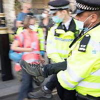 A protestestor is removed from Parliament Square by police during Extinction Rebellion protests urging government to take action on climate change.