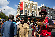 Eating jerk chicken on Monday 28th August 2016 at Notting Hill Carnival in West London. A celebration of West Indian / Caribbean culture and Europes largest street party, festival and parade. Revellers come in their hundreds of thousands to have fun, dance, drink and let go in the brilliant atmosphere. It is led by members of the West Indian / Caribbean community, particularly the Trinidadian and Tobagonian British population, many of whom have lived in the area since the 1950s. The carnival has attracted up to 2 million people in the past and centres around a parade of floats, dancers and sound systems.