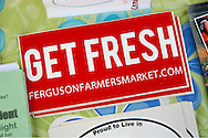 7 AUG. 2010 -- FERGUSON, MO. -- A bumper sticker promoting the Ferguson Farmers' Market rests on a table in the booth run by Kathy Noelker, Market Manager at the weekly market in Ferguson, Mo. Saturday, Aug. 7, 2010. The market is held on Saturdays, 8 am to 12 noon, through October in downtown Ferguson. Photo © copyright 2010 Sid Hastings.
