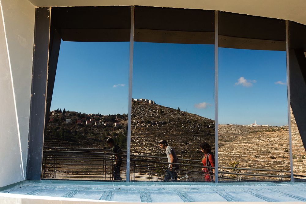 The West Bank Jewish settlement of Shiloh (L), a nearby Palestinian village (R) and Israeli visitors are reflected in the windows of the lookout tower at the archaeological park of Ancient Shiloh, which is located at the entrance to the modern Jewish settlement of Shiloh, south of the Palestinian West Bank town of Nablus, on January 1, 2017. Shiloh was the religious capital of Israel, an assembly place for the people of Israel and a center of worship before the first temple was built in Jerusalem. Its sacred area housed the Ark of Covenant.